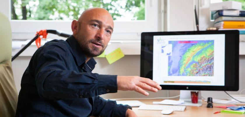 Portrait de Christian Sue devant son écran d'ordinateur avec une carte du Jura.