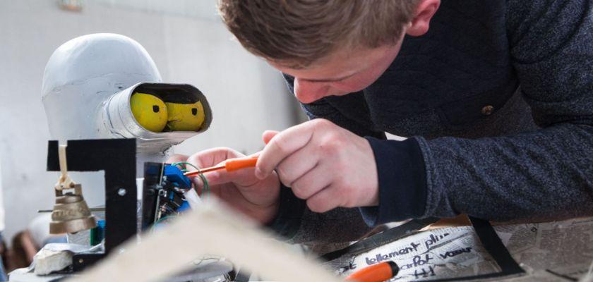 Un jeune garçon répare un robot à l'aide d'un tournevis.