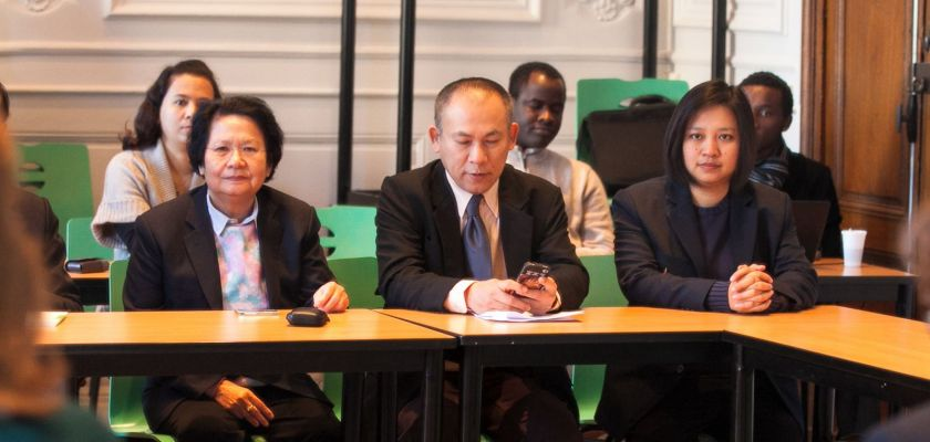 Trois membres de la délégation thailandaise installés à une table.