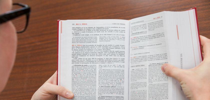 une jeune femme de dos lisant un livre de droit