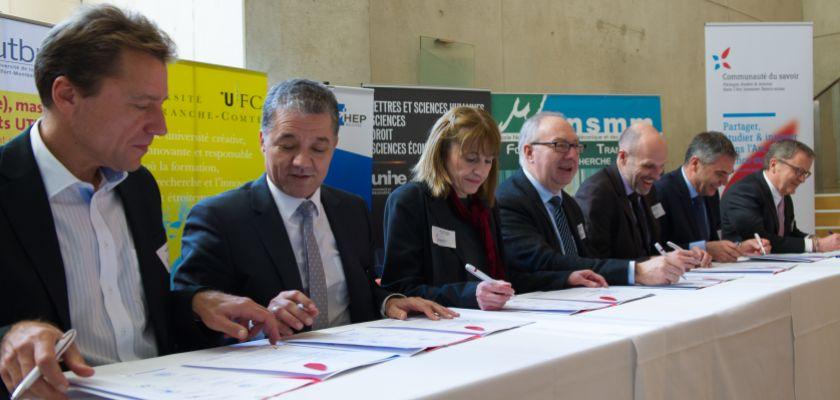 Une série de 7 directeurs d'établissements d'enseignement supérieur assis à une table pour la signature d'une convention.