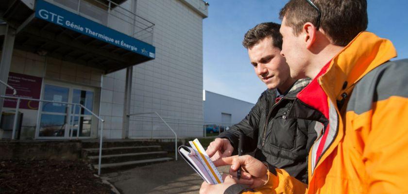 Deux étudiants observent un bâtiment de l'IUT depuis l'extérieur