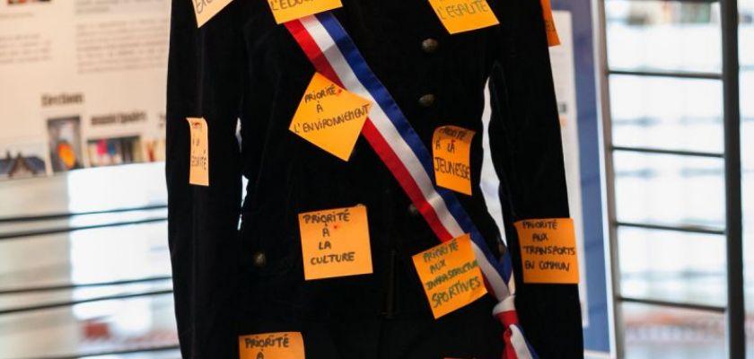 Un mannequin en habits officiels de maire avec des post it.