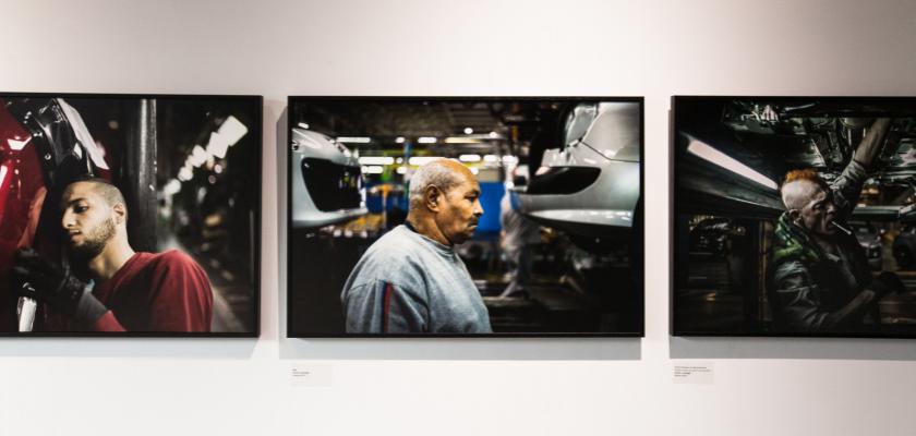 Trois photos d'ouvriers accrochées sur un mur.