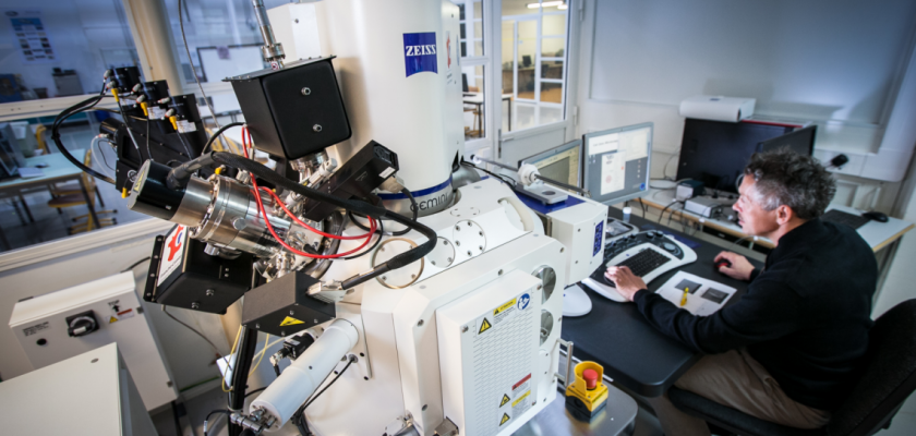 Au premier plan une énorme machine dont certains éléments évoquent un microscope et au second plan un homme derrière un ordinateur.
