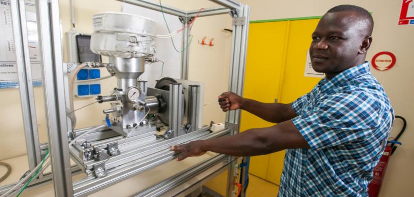 Un homme en train de démarrer un prototype de moteur Stirling