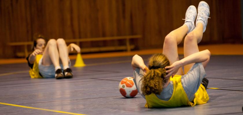 Deux jeunes filles en tenue de hanball en train de faire des exercices sportifs au sol