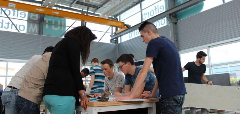Des étudiants autour d'une table dans un atelier.