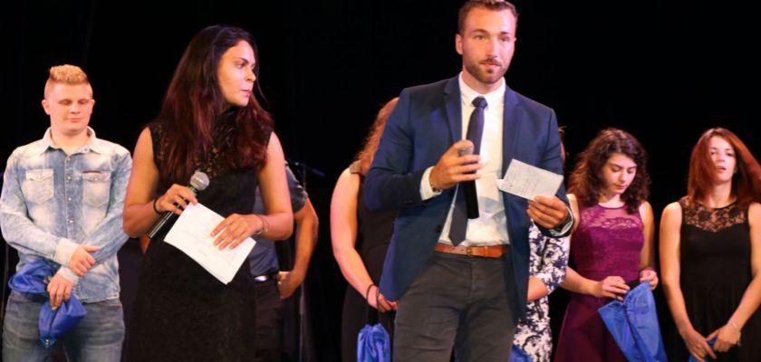 Antoine Mairot tenant un micro sur une scène, derrière lui des étudiants en tenue de gala qui tiennent des sacs cadeaux dans les mains.