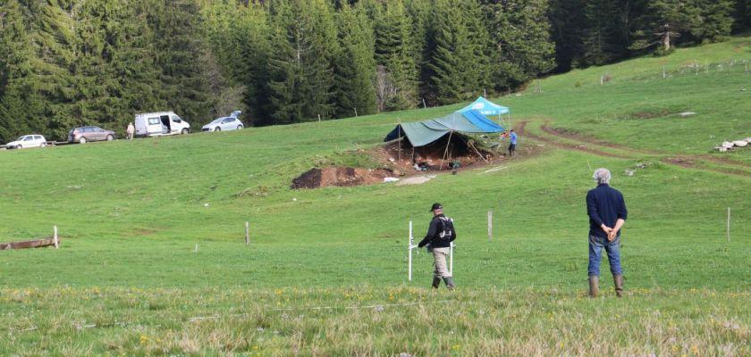Deux hommes de dos devant un chantier de fouilles en extérieur.