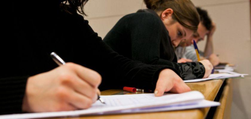 Des étudiants en train d'écrire sur des copies dans un amphithéâtre.