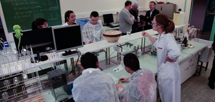 Des collégiens en blouse dans une salle de TP de Chimie