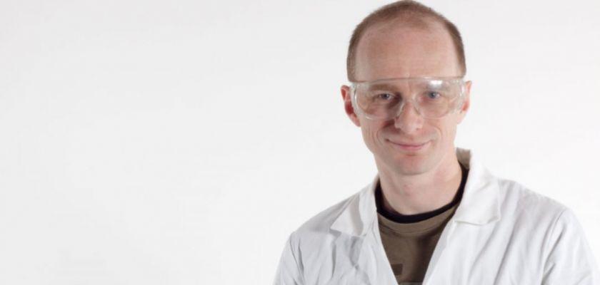 Portrait de Jérome Husson en blouse avec des lunettes de chimistes.