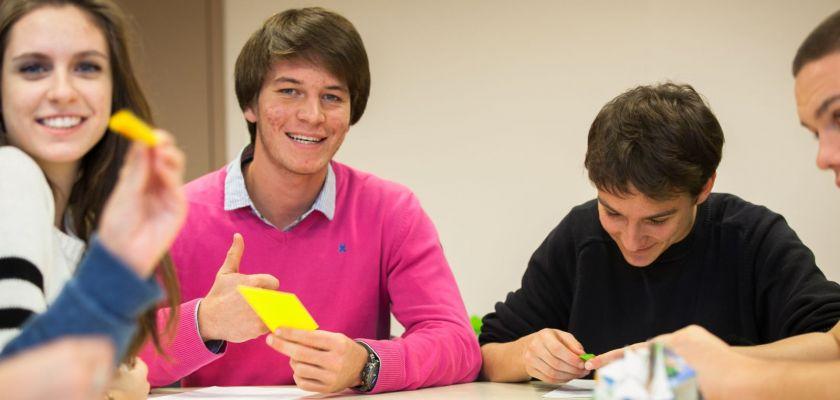 Trois lycéens souriant lors d'un atelier de pliages géométriques.