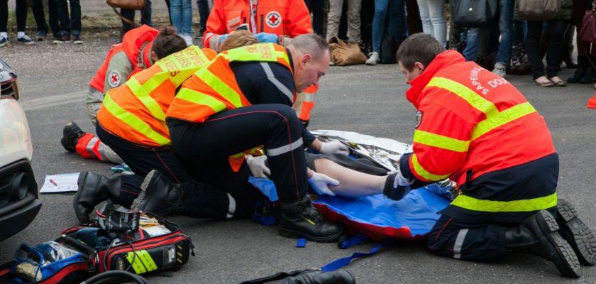Des pompiers et la croix rouge lors d'une simulation d'accident devant un public.