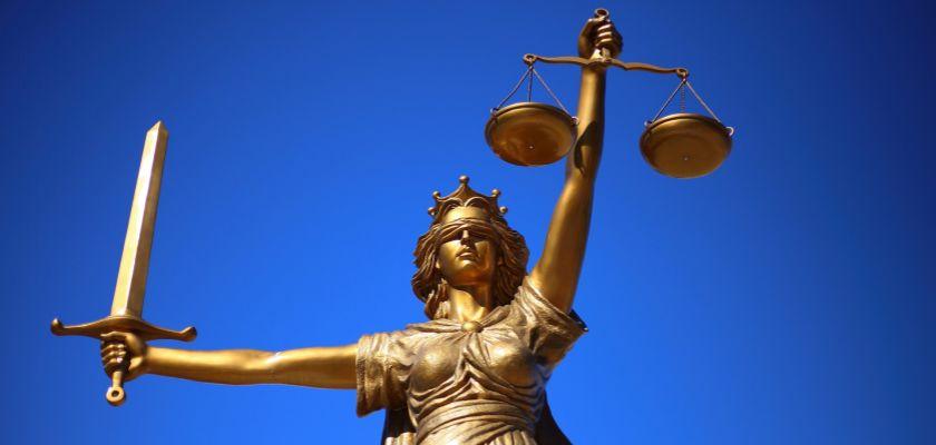 Un globe et une statuette de femme les yeux bandés tenant une balance