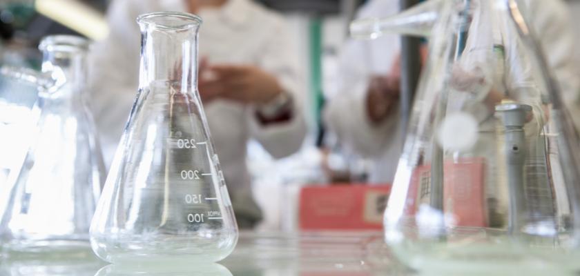 Des fioles Erlenmeyer dans un laboratoire de chimie. Des gens en blouse en arrière-plan dont on ne voit que les mains.