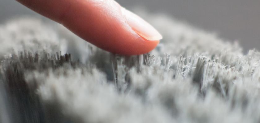 Un doigt de femme qui touche une surface laineuse.