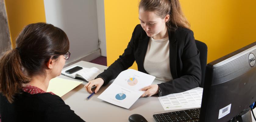 Deux jeunes femmes en tenue de travail en conversation à un bureau.