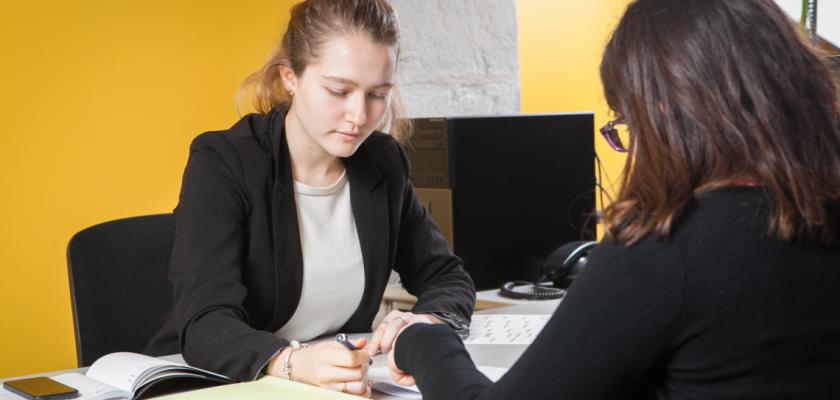 Une situation de travail avec deux jeunes femmes dans un bureau.