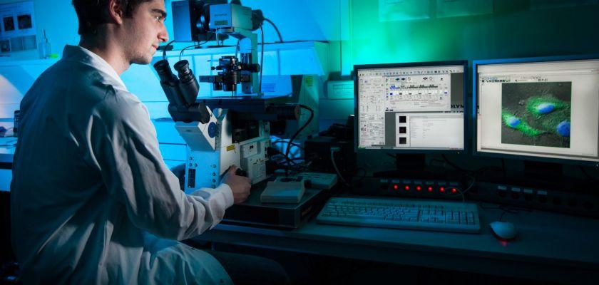 homme en blouse devant un microscope