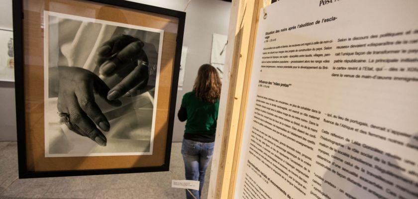 Vue de l'exposition, gros plan sur une photo de mains et un panneau, une femme de dos dans la salle en arrière plan.