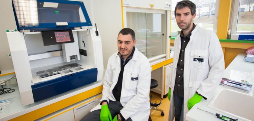 Paul Peixoto et Eric Hervouet, en blouse blanche, posent devant un robot d'immunoprécipitation.