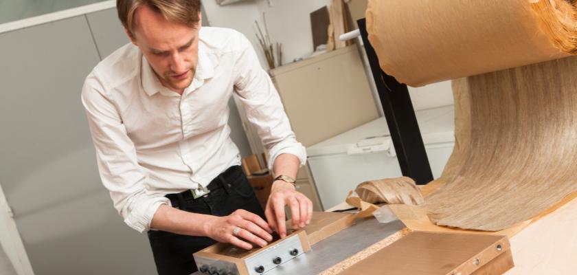 Un homme penché sur une boite à côté de laquelle figure une table de violon. A côté de lui, un rouleau d'un matériau qui ressemble à du papyrus.