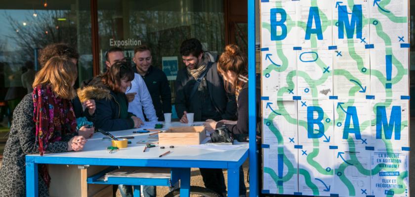 Un atelier mobile avec des affiches indiquant BAM et différentes personnes souriantes autour d'un plan de travail.