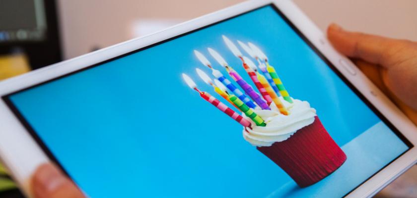 Des mains tiennent une tablette sur laquelle on voit un gateau d'anniversaire.