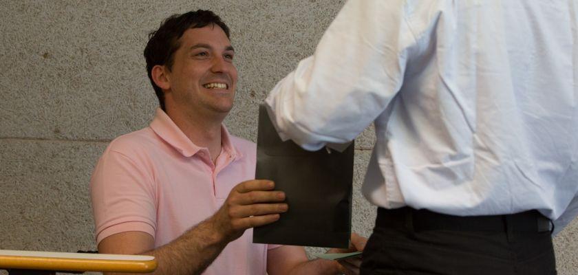 Un homme en fauteuil roulant souriant en train de recevoir un diplôme