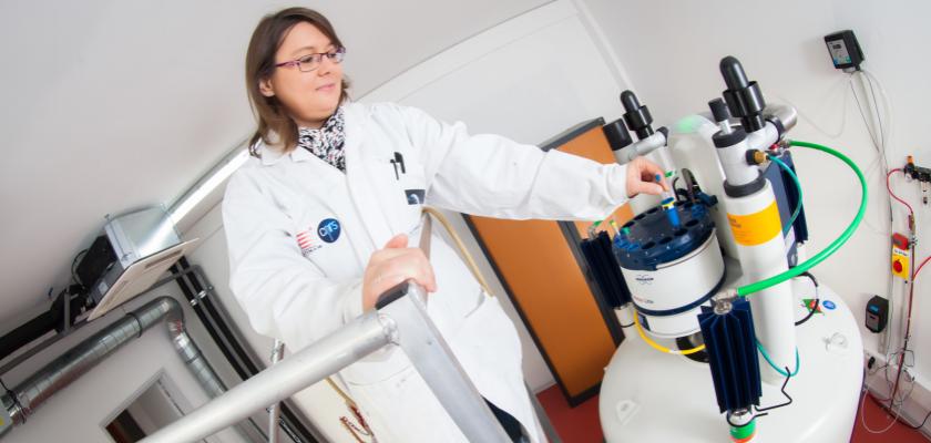 Une femme en blouse en train d'insérer un tube à essai dans un appareil de spectroscopie RMN