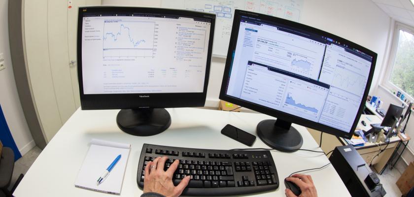 Deux écrans d'ordinateur avec des courbes et les mains d'une personne sur un clavier et tenant une souris.