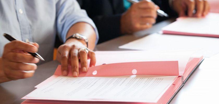 Des mains qui tiennent un stylo, en train de signer un document sur un parapheur.
