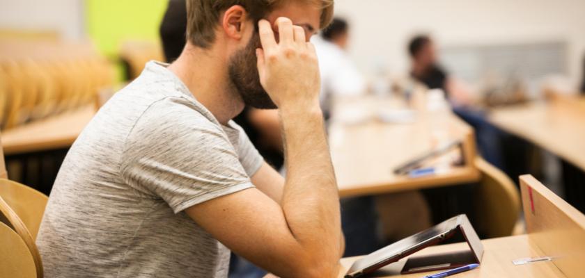 Un étudiant devant sa tablette dans un amphi