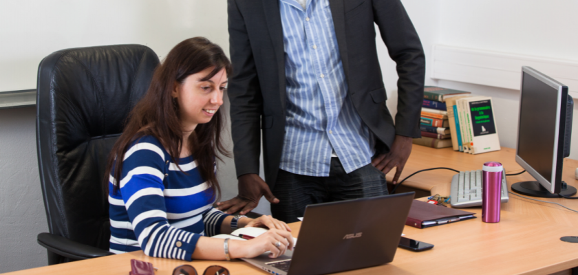Iana Atanassova devant un ordinateur. Un collègue se tient derrière elle.