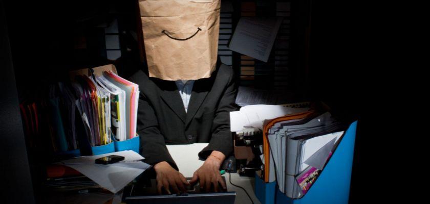 Un homme en costume dans un bureau sombre avec un sace en papier sur la tête et un sourire dessiné sur le sac.