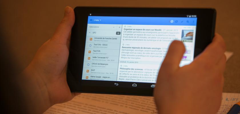 Deux mains tenant une tablette numérique