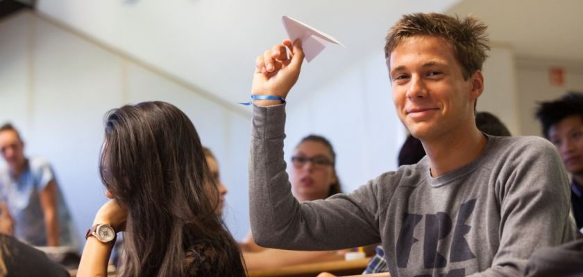 Un étudiant brandit un avion en papier.