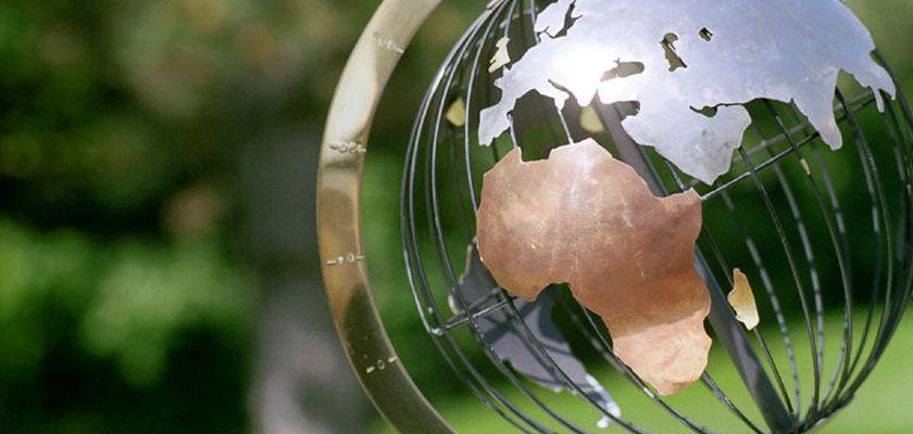 Un globe terrestre transprent sur fond de végétation.