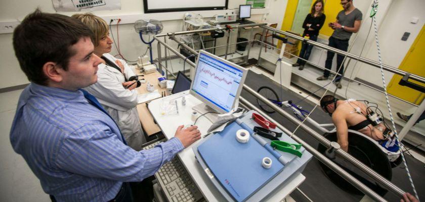 Plate-forme EPSI : deux chercheurs derrière des écrans observent un sportif sur un tapis roulant.