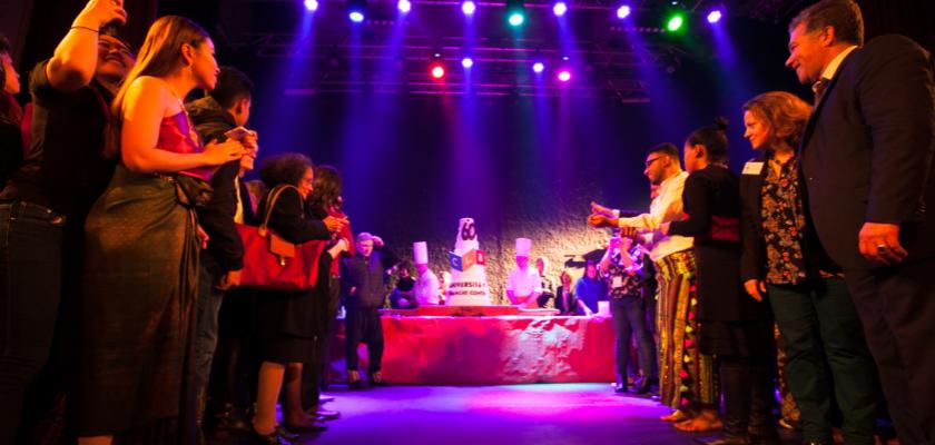 Sur la scène du kursaal, les gens forment une haie d'honneur au fond de laquelle se trouve un gâteau estampillé CLA.