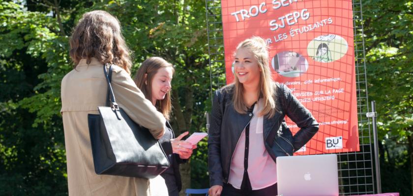 Une jeune fille sur un stand en train de parler à deux personnes de dos.