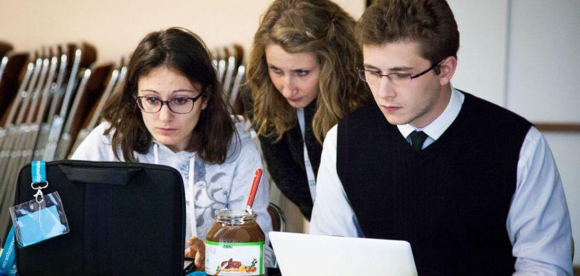 Trois étudiants l'air préoccupé devant leurs ordinateurs portables avec un pot de pâte à tartiner au milieu.