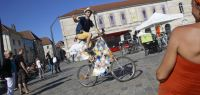Place de la révolution à Besançon : un jeune homme perché sur un vélo très haut fait signe au photographe.