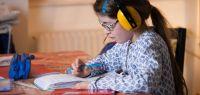 Une fillette fait ses devoirs avec un casque anti-bruit sur les oreilles.