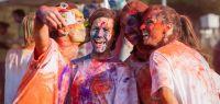 Quatre étudiants recouverts de farine colorée en train de faire un selfie.