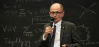 Christian Le Merdy parle au micro devant un tableau noir rempli de symboles mathématiques.