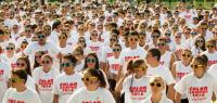 """Un ensemble d'étudiants portant tous le même tee shirt blanc marqué """"color campus 2016"""" et des lunettes de soleil colorées."""