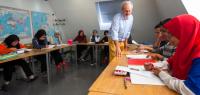 Une salle de classe avec des tables installées en ovale. Au milieu, un enseignant s'adresse à des étudiants malaisiens installés à ces tables.